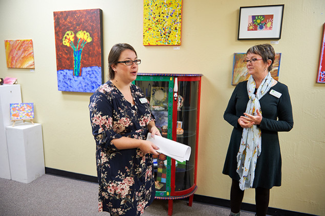 Angela Grech and Lisa Folsom-Ernst amid a display of artwork by clients.