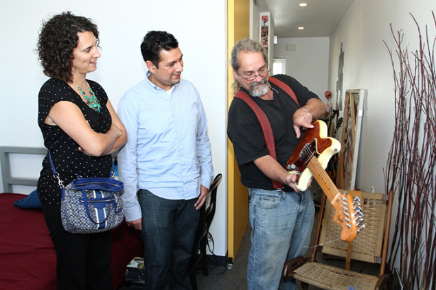 Resident Bill Fisher shows Dana Trujillo and Joey Aguilar how he restored a found guitar.